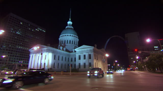 ws traffic moving on road infront of st louiss courthouse at night / st louis, missouri, united states  - ミズーリ州 セントルイス点の映像素材/bロール