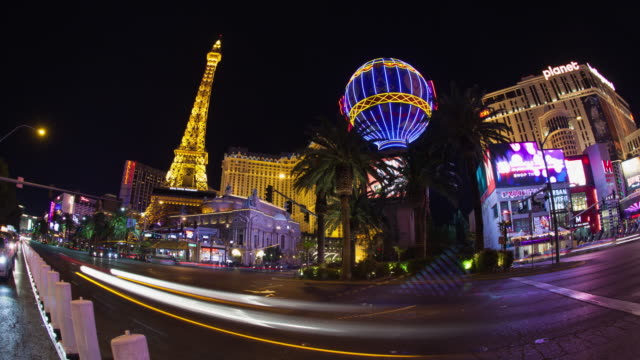 ws t/l pan traffic moving on street at night, hotels buildings in background / las vegas, nevada, united states  - las vegas replica eiffel tower stock videos & royalty-free footage