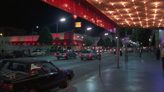 ms ts pan traffic moving on street in city at night - theatre banner commercial sign stock videos & royalty-free footage