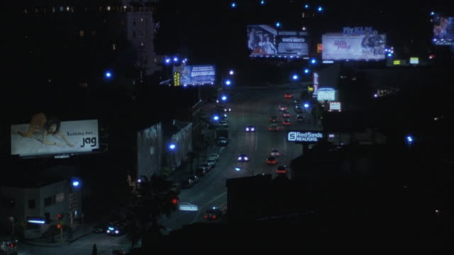 traffic moving on the sunset boulevard in los angeles at night. - sunset boulevard stock-videos und b-roll-filmmaterial