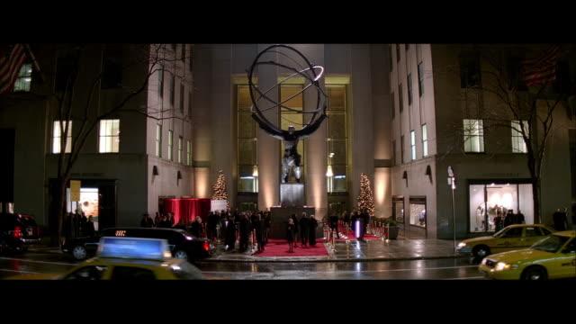 vídeos de stock e filmes b-roll de ws traffic moving past a red carpet event at rockefeller center / new york city, new york, united states - estátua de atlas