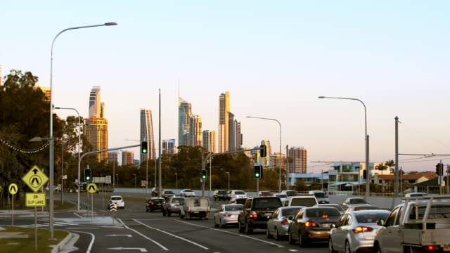 Traffic moving through an intersection with skyline at sunset