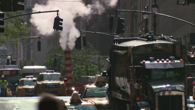 traffic navigates around a steam pipe in the middle of the street.  a garbage truck rolls by. - garbage truck stock videos and b-roll footage