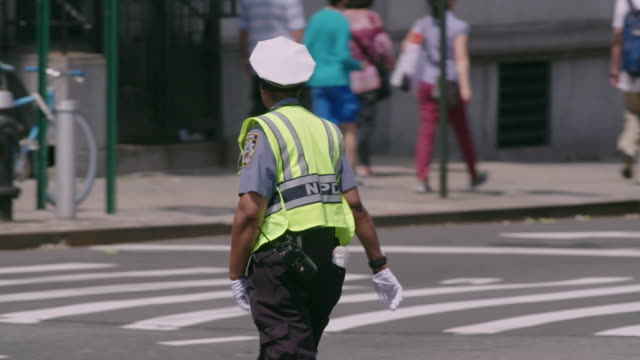 Traffic officer directs traffic on busy New York City intersection on hot summer day.