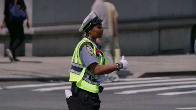 nypd traffic officer energetically directs traffic on new york city intersection. - trillerpfeife stock-videos und b-roll-filmmaterial