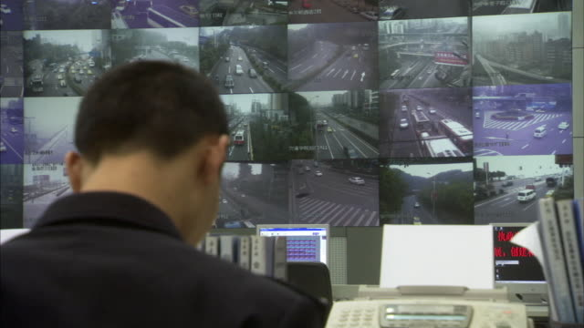 vídeos y material grabado en eventos de stock de ms pan traffic officials watching multi-vision video screens showing traffic conditions / chongqing, sichuan province, china  - big brother