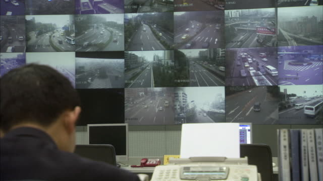 ms pan traffic officials watching multi-vision video screens showing traffic conditions / chongqing, sichuan province, china  - surveillance stock videos & royalty-free footage
