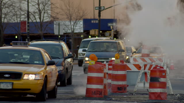 Traffic on 7th Avenue drives around a steam pipe and construction area.