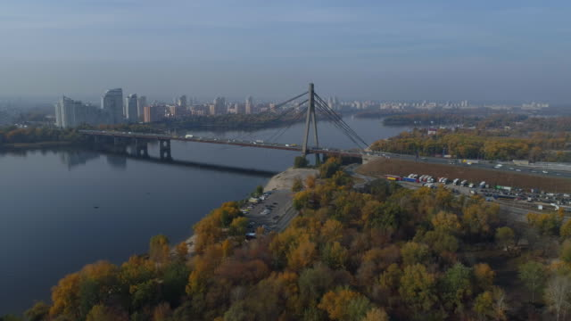 traffic on a bridge across a wide river on an autumn day. aerial view. - キエフ市点の映像素材/bロール