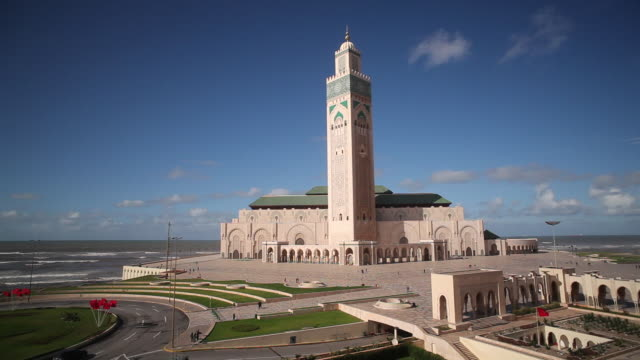 traffic on a curve passes the hassan ii mosque. - casablanca morocco stock videos & royalty-free footage