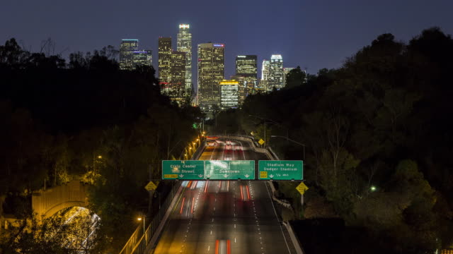 T/L, HA, LS Traffic on a freeway at night with Los Angeles in distance / Los Angeles, USA