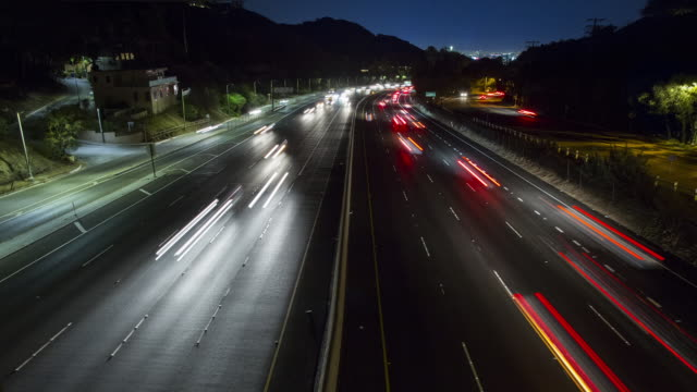 stockvideo's en b-roll-footage met t/l, ls traffic on a freeway at night with los angeles in distance / los angeles, usa - lichtspoor lange sluitertijd