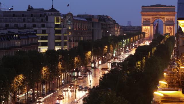 vidéos et rushes de t/l ws ha traffic on avenue des champs-elysees, arc de triomphe in background, dusk to night / paris, ile de france, france - arc élément architectural