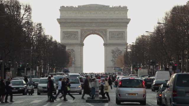 ws traffic on avenue des champs-elysees with arc de triomphe in background, paris, france - arc de triomphe paris stock videos & royalty-free footage
