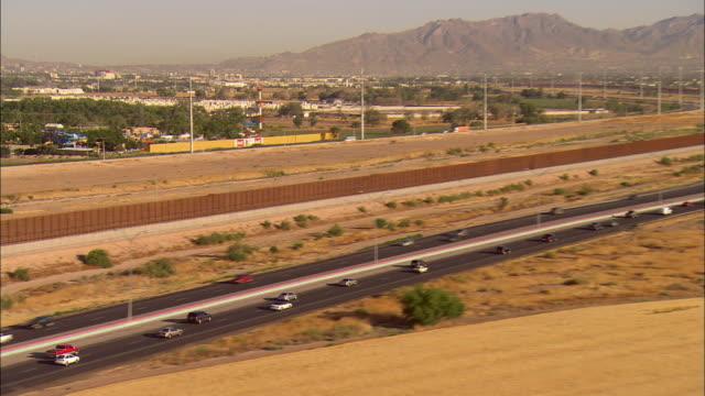 AERIAL Traffic on Border Highway along new border 'wall', El Paso, Texas, USA