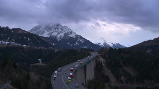 traffic on brenner highway with europa bridge at dusk twilight. cloudy sky and snow covered mountains in springtime. - brennero stock videos and b-roll footage