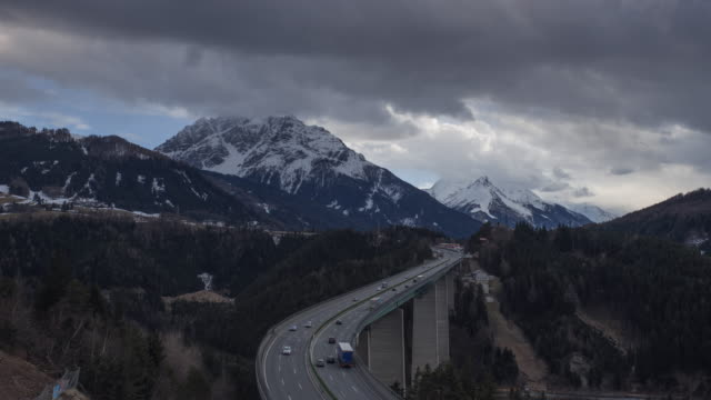 traffic on brenner highway with europa bridge. cloudy sky and snow covered mountains in springtime. - brennero stock videos and b-roll footage