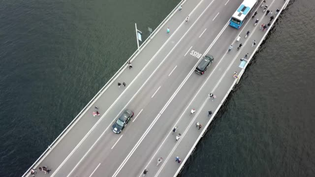 traffic on bridge in central stockholm seen from above, meeting buses - stockholm stock videos & royalty-free footage