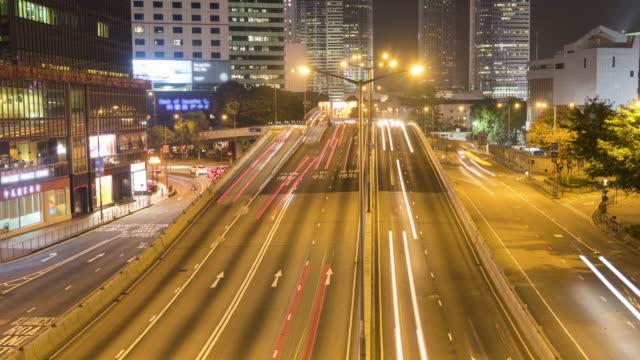 vidéos et rushes de circulation sur une route très fréquentée pendant la nuit - île de hong kong