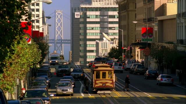 ws, traffic on california street, bay bridge visible in background, san francisco, california, usa - カリフォルニアストリート点の映像素材/bロール