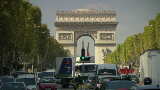 vidéos et rushes de ms traffic on champs-elysees with arc de triomphe in background / paris, france - arc élément architectural
