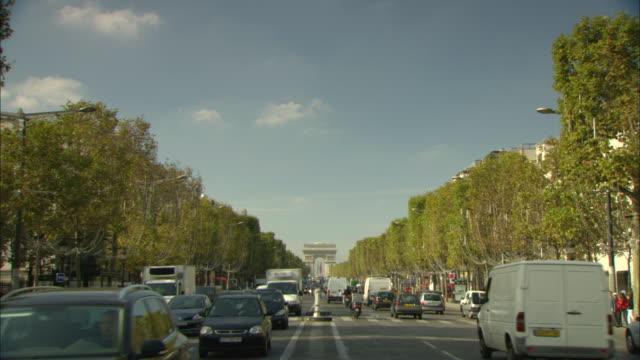 vidéos et rushes de ws traffic on champs-elysees with arc de triomphe in background / paris, france - arc élément architectural