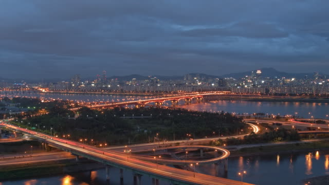 T/L WS HA Traffic on Cheongdam Bridge with city skyline in distance, day to night / Seoul, South Korea