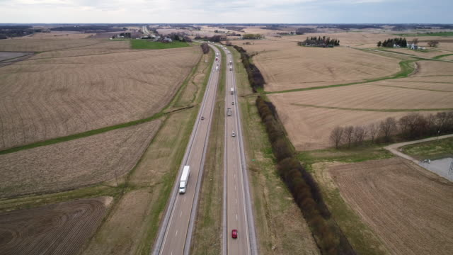 traffic on chicago - kansas city expressway surrounded by the agricultural fields in the springtime, nearby lyndon township, illinois, usa. cinematic aerial drone video with the static camera. - illinois stock videos and b-roll footage