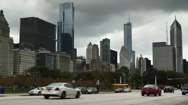 ws traffic on city road with skyscrapers in background, chicago, illinois, usa - 固定撮影点の映像素材/bロール