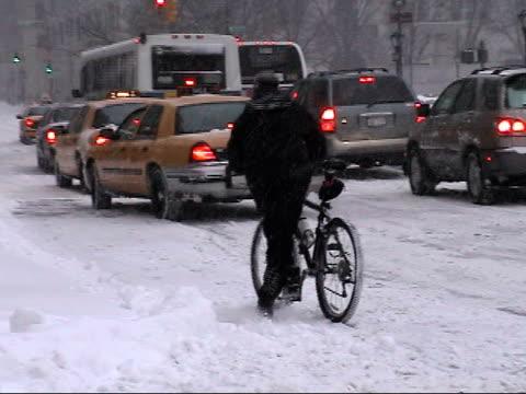 MS, Traffic on city street in heavy snow, New York City, New York, USA