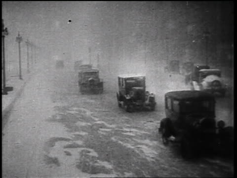 b/w 1935 traffic on city street in snowstorm / educational - 1935 stock videos & royalty-free footage