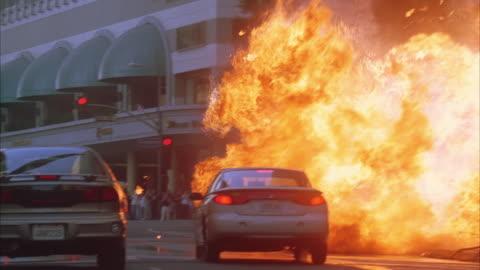 vidéos et rushes de ms traffic on city street, large fireball explosion between buildings - terrorisme
