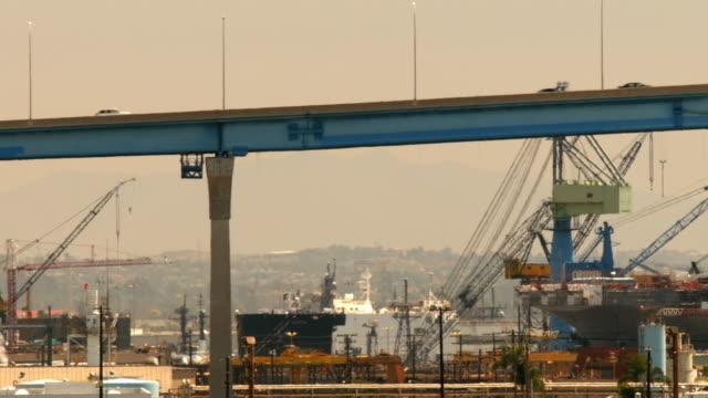 ls pan traffic on coronado bridge near oil refinery and naval shipyard where battleship is under repair / san diego, california, usa - warship stock videos & royalty-free footage