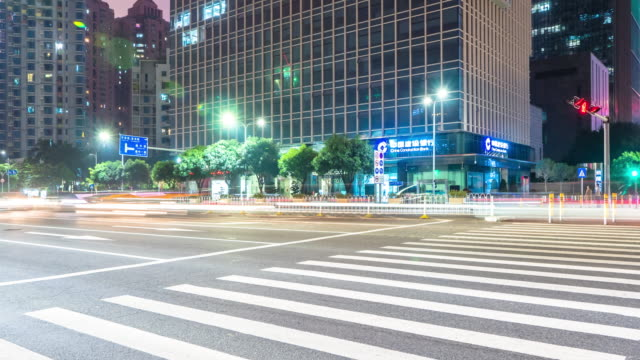 traffic on crossing of city street and building in shenzhen at night timelapse 4k - urban road stock videos & royalty-free footage