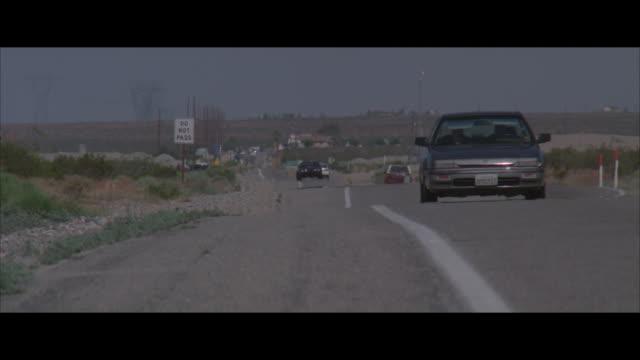 ms, pan, traffic on desert road, black pontiac approaching to camera, usa - ポンティアック点の映像素材/bロール
