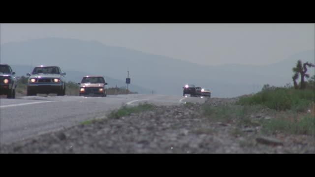 ms, pan, traffic on desert road, mountains in background, usa - ポンティアック点の映像素材/bロール