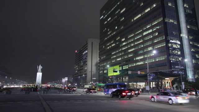 WS Traffic on downtown street at night with Yi sun-sin statue / Seoul, South Korea