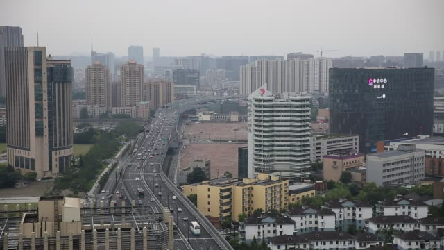traffic on elevated highway amidst buildings in city - hangzhou stock videos & royalty-free footage