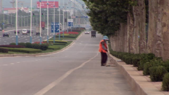 ws pan traffic on freeway/ street sweeper on side of road with broom/ jinan, china - roadside stock videos & royalty-free footage