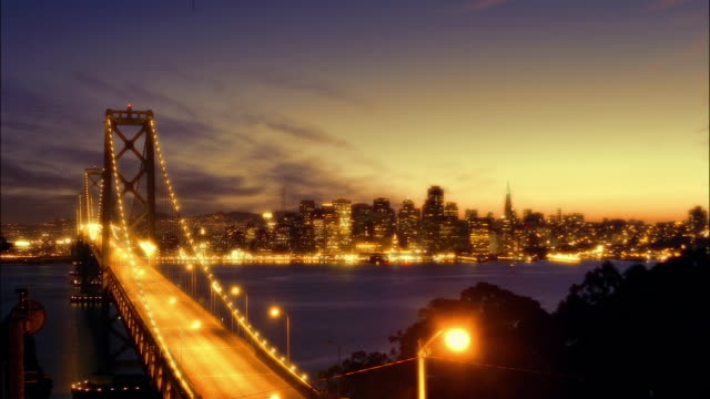 T/L WS traffic on Golden Gate Bridge and cityscape at dusk and night, San Francisco, California, USA