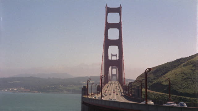 vídeos de stock, filmes e b-roll de ws ha pan traffic on golden gate bridge with cityscape over bay / san francisco, california, usa - 1965