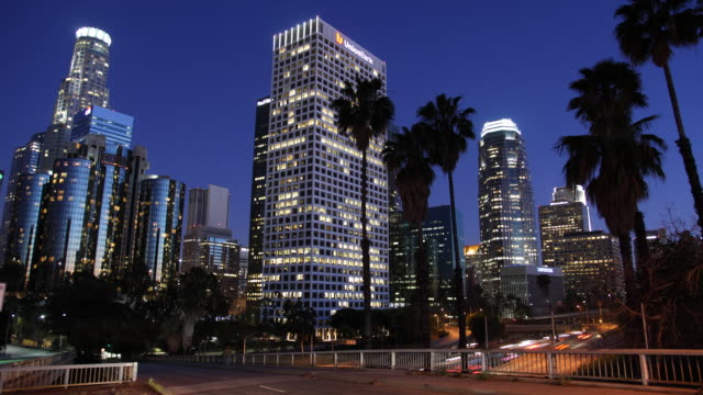 T/L WS Traffic on highway and illuminated skyscrapers, dusk to night / Los Angeles, California, USA