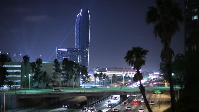 ws traffic on highway and skyscraper illuminated at night / los angeles, california, usa - サーチライト点の映像素材/bロール