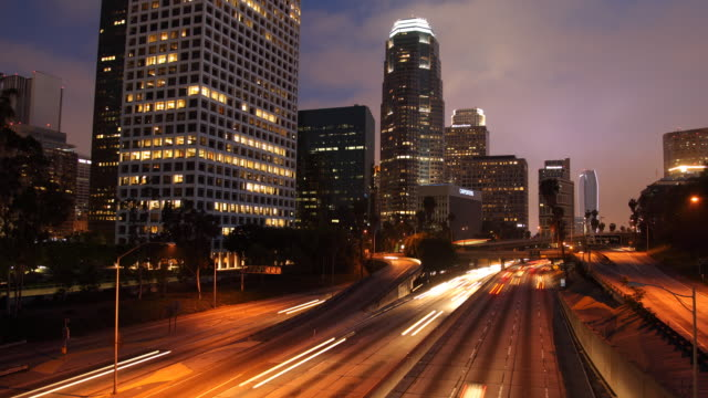 T/L WS Traffic on highway and skyscrapers, dusk to night / Los Angeles, California, USA