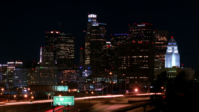 t/l, ws, traffic on highway at night, cityscape in background, los angeles, california, usa  - hinweisschild stock-videos und b-roll-filmmaterial