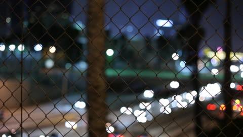 vídeos y material grabado en eventos de stock de ws selective focus traffic on highway at night seen through chain link fence / los angeles, california, usa - enfoque en primer plano
