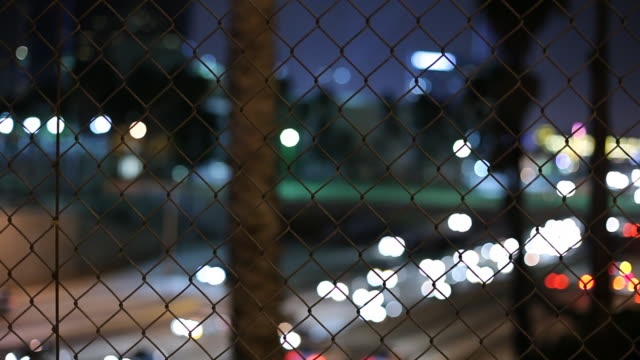 ws selective focus traffic on highway at night seen through chain link fence / los angeles, california, usa - 後ろボケ点の映像素材/bロール