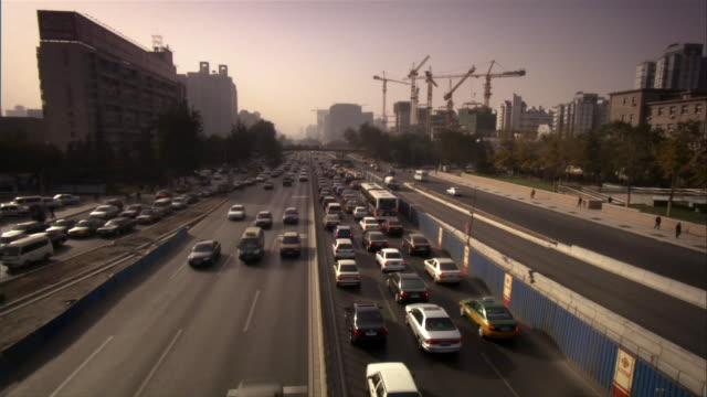 ms, ha, traffic on highway, construction site in background, beijing, china - privatfahrzeug stock-videos und b-roll-filmmaterial