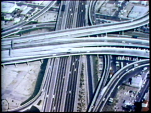 1973 MONTAGE AERIAL WS Traffic on highway/ Highway running through citscape/ USA/ AUDIO