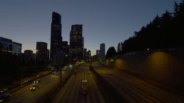 high angle wide shot traffic on highway in seattle at dusk - コロンビアセンター点の映像素材/bロール